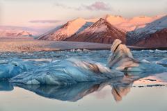view across the calm water of jokulsarlon glacial lagoon towards snow-capped  - stock photo