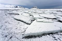 Winter view over slabs of broken lake ice covered in snow towards kirkjufell  Stock Photos
