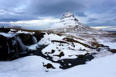 kirkjufell (church mountain) covered in snow with a frozen river and waterfal - stock photo