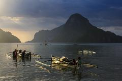 Outrigger boat at sunset in the bay of el nido, bacuit archipelago, palawan,  Stock Photos