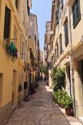 narrow street with lady sweeping, old town, corfu town, unesco world heritage - stock photo