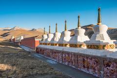 Stock Photo of tibetan buddhist stupas are shine under the sunset light