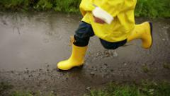 Young Boy Running Through Puddle - stock footage