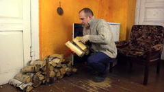 Villager man carry armful of firewood and axe near rural stove Stock Footage