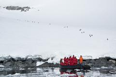 People in small inflatible zodiac boats approaching Cuverville Island. - stock photo