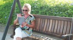 Woman using digital tablet on swing Stock Footage