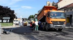 Roadwork. Truck filling paving machine with asphalt. Workers. Steamroller. Stock Footage
