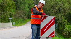 Worker with wrench on the bridge repairing road sign Stock Footage