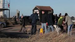 People and dogs meeting at seaside car park Stock Footage