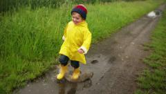 Young Boy Running Through Puddle Stock Footage