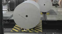 Big paper rolls being prepared for the production of leaflets - stock footage