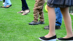 Detail of children dancing on the lawn, panning Stock Footage