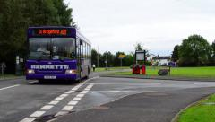 A Purple Bus Pulls Up to a Bus Stop in a Rural Village Stock Footage