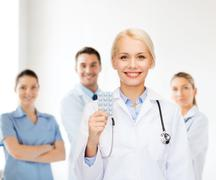 Smiling female doctor with pills Stock Photos