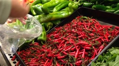 Woman selecting fresh hot chili pepper in grocery store Stock Footage