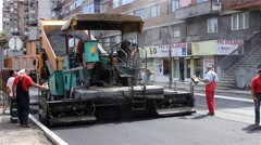 Roadworks. Machine for asphalt. Paving. Asphalting. Workers control operation. - stock footage