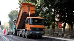 Truck pouring asphalt in paving machine. Second truck passes through the shot. Stock Footage