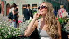 Portrait of young woman wearing retro round sunglasses waiting for a friend Stock Footage