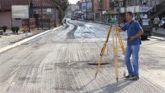Surveyor on construction site measuring with modern survey equipment.Medium shot Stock Footage