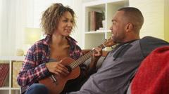Cute black girlfriend serenading her boyfriend with ukulele Stock Footage