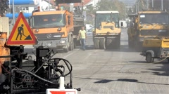Roadwork. Workers. Machines. Road rollers and trucks preparing for paving street Stock Footage