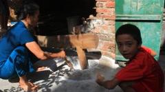 Farmers pounding rice into flour, Asia Stock Footage