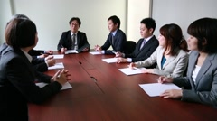 Japanese business people having a meeting around a wooden desk in a modern Stock Footage