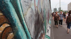 People walk along the remains of Berlin wall - stock footage