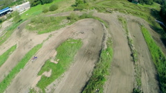 Racer on motocross track slowing down while cornering on dirt air shot - stock footage
