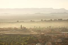 view over the town of tinerhir soon after sunrise showing smoke rising from t - stock photo