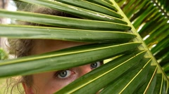 Woman Looking through Coconut Palm Leaves. Slow Motion. Stock Footage