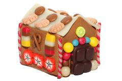 a handmade fimo marzipan house, with cookies, candies, fruits and flowers - stock photo
