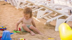 Little Boy Plays With Toys In Sand Stock Footage