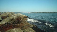 Ocean waves crash against scenic rocky Maine coast, camera pan Stock Footage