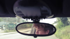 Man in rearview mirror driving car Stock Footage