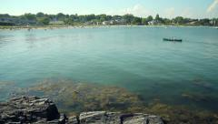 Canoeist paddles into Willard Beach, South Portland, Maine, wide shot Stock Footage
