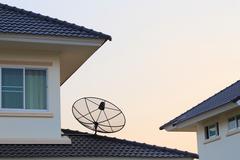 Satellite dish and tv antennas on the house roof Kuvituskuvat