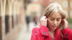 Mid shot attractive blonde woman putting headphones in whilst walking city Stock Footage