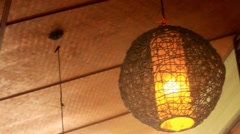 Wicker round lantern hanging and swaying in wind at cafe Stock Footage