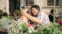 Young couple taking a selfie together on the cafe terrace on sunny day Stock Footage