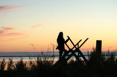 Silhouette of a woman on a stile at twilight time Stock Photos