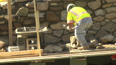 Stone wall construct breaking stones telephoto Stock Footage