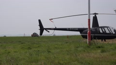 Airport bird clearance vehicle on runway with helicopter Stock Footage