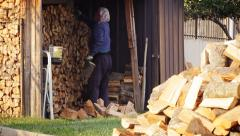 Old man working at garden by stacking pieces of wood Stock Footage