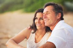 mature couple enjoying sunset on the beach - stock photo