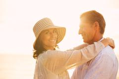 Mature couple in love on the beach at sunset Stock Photos