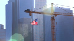 Stock Video Footage of American Flag in Sunshine with skyscraper buildings and construction crane