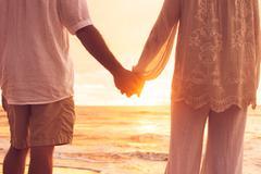 Senior couple holding hands enjoying at sunset Stock Photos
