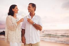 romantic couple drinking champagne on the beach at sunset - stock photo