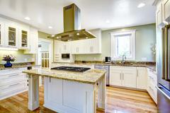 kitchen island with built-in stove, granite top and hood - stock photo